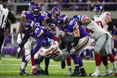 Oct 3, 2016; Minneapolis, MN, USA; New York Giants running back Orleans Darkwa (26) is tackled by Minnesota Vikings defensive tackle Linval Joseph (98) and defensive end Brian Robison (96) during the first quarter at U.S. Bank Stadium. Mandatory Credit: Brace Hemmelgarn-USA TODAY Sports