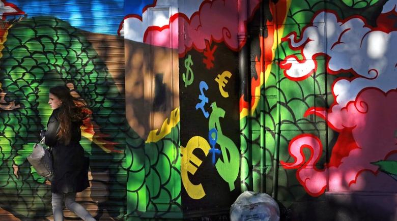 A woman walks past graffiti near the Temple Bar area of Dublin November 7, 2013. REUTERS/Cathal McNaughton
