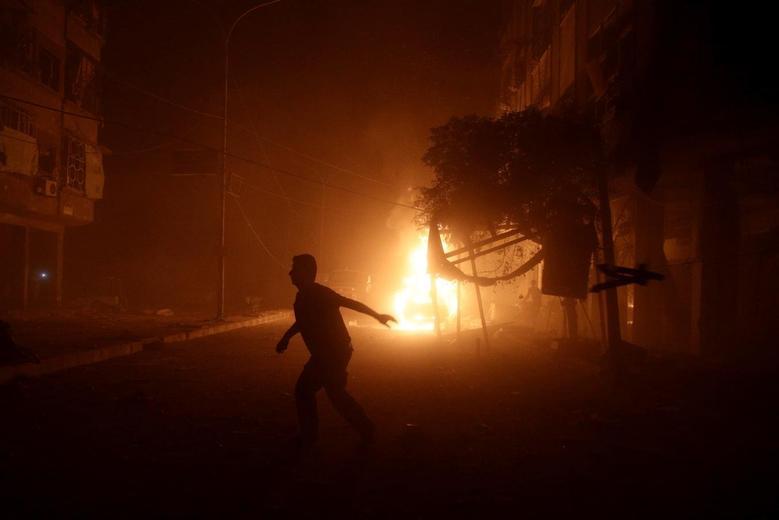 A man runs near a burning car after an airstrike in the rebel held Douma neighbourhood of Damascus, Syria October 3, 2016. REUTERS/Bassam Khabieh