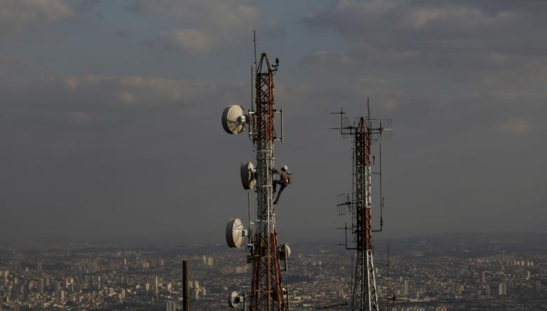 A man works on a tower with various types of directional antennas in Sao Paulo August 5, 2015. REUTERS/Nacho Doce