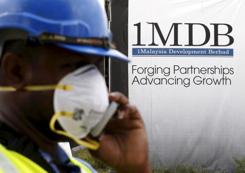 A construction worker talks on the phone in front of a 1Malaysia Development Berhad (1MDB) billboard at the Tun Razak Exchange development in Kuala Lumpur, Malaysia, February 3, 2016.   REUTERS/Olivia Harris/File Photo