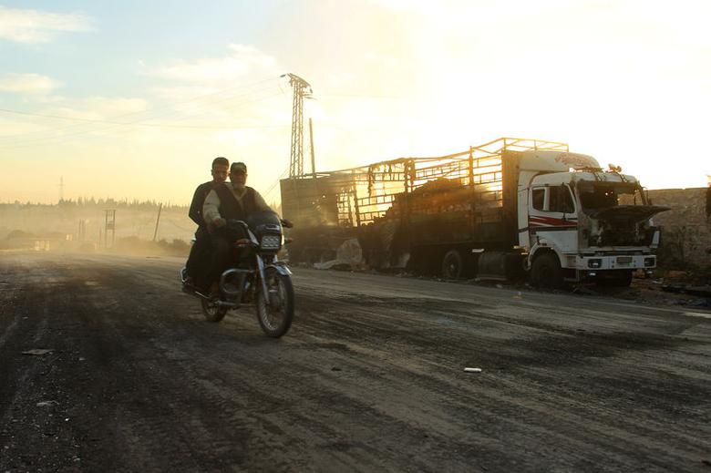 Men drive a motorcycle near a damaged aid truck after an airstrike on the rebel held Urm al-Kubra <p>To learn more about clothes online shopping visit <a href=
