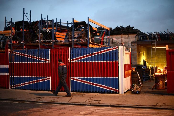 A man walks past a car scrap yard in east London January 25, 2013.   REUTERS/Paul Hackett/File Photo
