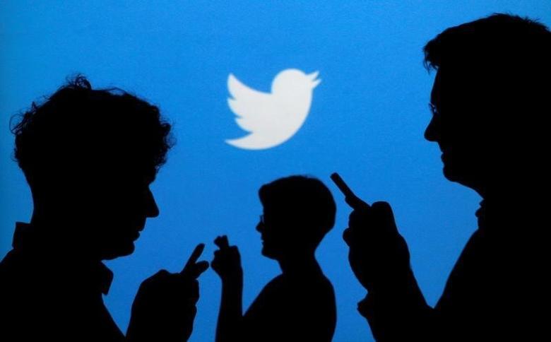2013年9月27日,持手机的人影映在有Twitter企业标识的背景上。REUTERS/Kacper Pempel/Illustration/File Photo
