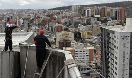 Unos trabajadores sobre el techo de un edificio en Quito, sep 7, 2011. La tasa anual de inflación en Ecuador se desaceleró a 1,30 por ciento en los últimos 12 meses a septiembre frente a igual periodo del año previo, informó el jueves la agencia oficial de estadística.  REUTERS/Guillermo Granja