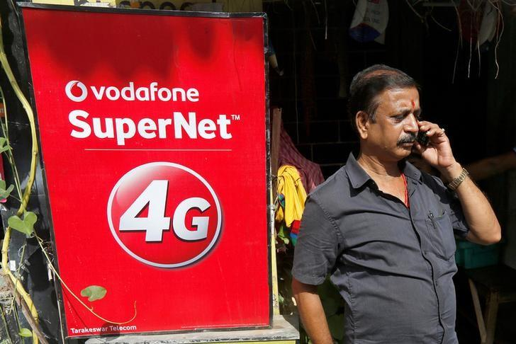 A man speaks on his mobile phone next to a Vodafone advertisement in Kolkata, India, September 26, 2016. REUTERS/Rupak De Chowdhuri/Files