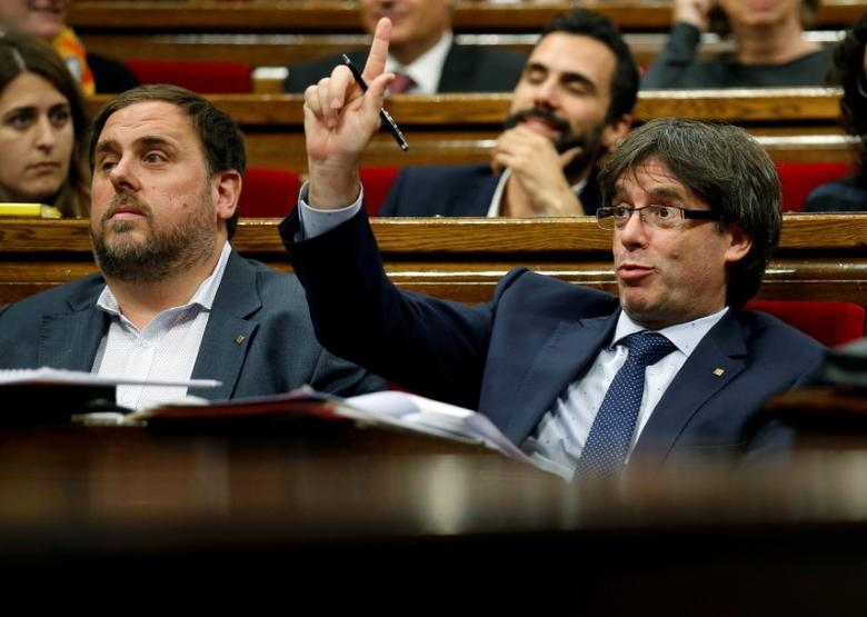 Catalonia's President Carles Puigdemont (R) gestures next to Oriol Junqueras, leader of Esquerra Republicana de Catalunya (ERC), during a confidence vote session at Catalan Parliament in Barcelona, Spain September 29, 2016. REUTERS/Albert Gea