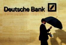 Прохожий у офиса Deutsche Bank в Лондоне. 5 декабря 2013 года. Катарские инвесторы - крупнейшие акционеры Deutsche Bank - не планируют продавать акции банка и могут докупить их, если банк пойдёт на докапитализацию, сказали Рейтер источники, знакомые с инвестиционной стратегией Катара. REUTERS/Luke MacGregor/File Photo