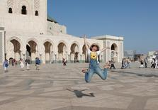 Chinese tourists jump as they pose for photographs at the esplanade of the Hassan II Mosque in Casablanca, October 6, 2016.  REUTERS/Youssef Boudlal