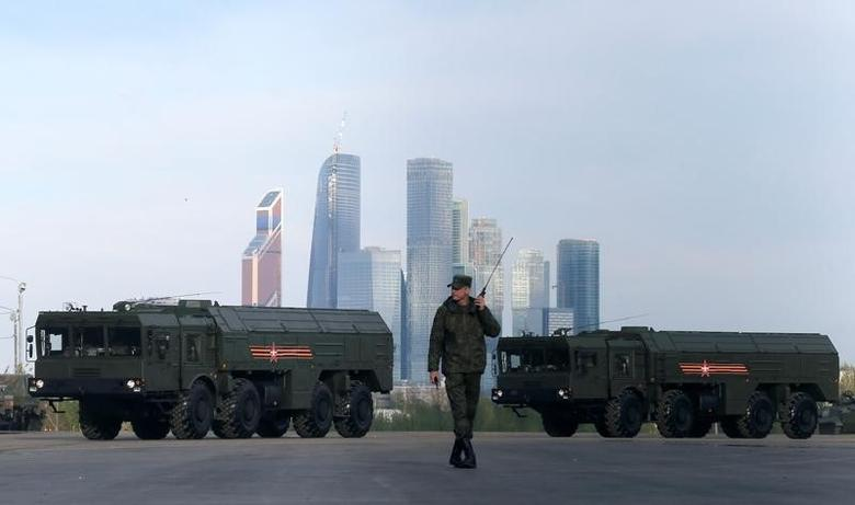 A Russian serviceman walks past Russian Iskander-M missile launchers before a rehearsal for the Victory Day parade, with the Moscow International Business Center also known as ''Moskva-City'' seen in the background, at a range in Moscow, Russia, May 5, 2016. REUTERS/Maxim Shemetov