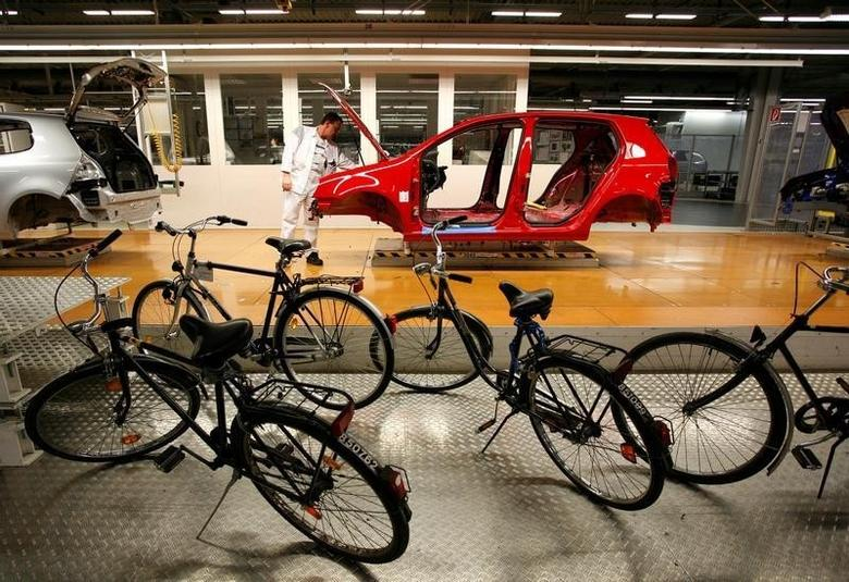 Bicycles are parked beside the production line while an employee works on a Volkswagen Golf car at the Volkswagen headquarters in Wolfsburg February 15, 2007. REUTERS/Christian Charisius/File Photo