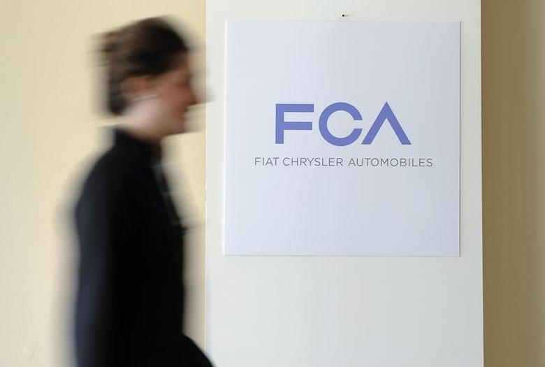 A woman walks past a logo of Fiat Chrysler Automobiles (FCA) in Turin March 31, 2014.   REUTERS/Giorgio Perottino