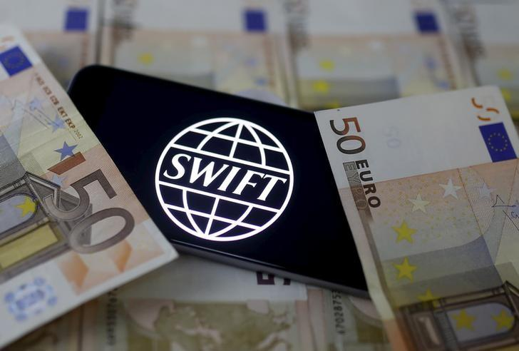 Swift code bank logo is displayed on an iPhone 6s on top of Euro banknotes in this picture illustration, January 26, 2016.   REUTERS/Dado Ruvic/Illustration/File Photo