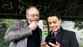 Games of Thrones star Liam Cunningham smiles together with his supporter Syrian migrant Hussam Alheraky as he made a surprise vist in Stuttgart, Germany, October 11, 2016. REUTERS/Reuters Tv