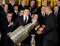 U.S. President Barack Obama (R) helps National Hockey League Pittsburgh Penguins' Captain Sidney Crosby with the Stanley Cup during a ceremony to honor the winners of the 2016 Stanley Cup, in the East Room of the White House, in Washington, October 6, 2016.      REUTERS/Mike Theiler