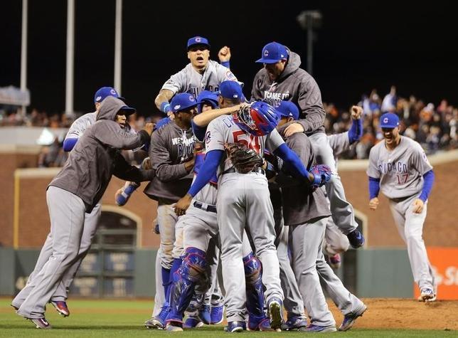 10月11日、MLBナ・リーグ地区シリーズ第4戦、カブスはジャイアンツに6─5で勝利して対戦成績を3勝1敗とし、リーグ優勝決定シリーズに進出した。写真は勝利を喜ぶカブスの選手たち(2016年 ロイター/John Hefti-USA TODAY Sports)