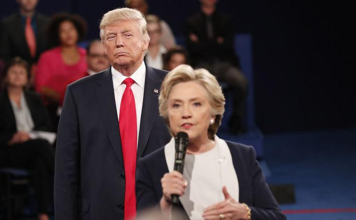 Donald Trump listens as Hillary Clinton answers a question from the audience during their presidential town hall debate at Washington University in St. Louis, Missouri, October 9, 2016. REUTERS/Rick Wilking
