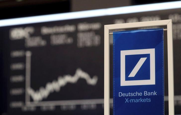 A Deutsche Bank banner is pictured in front of the German share price index, DAX board, at the stock exchange in Frankfurt, Germany September 30, 2016. REUTERS/Kai Pfaffenbach/Files