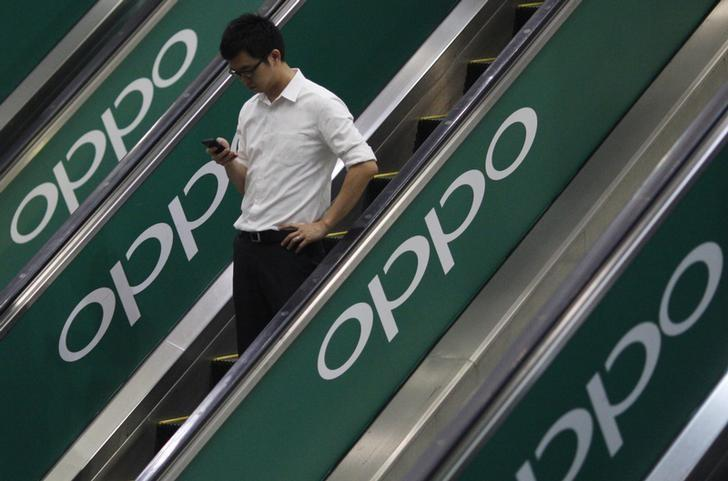A commuter using his mobile phone passes an advertisement of Chinese smartphone maker Oppo at a train station in Singapore May 8, 2014.  REUTERS/Edgar Su/Files