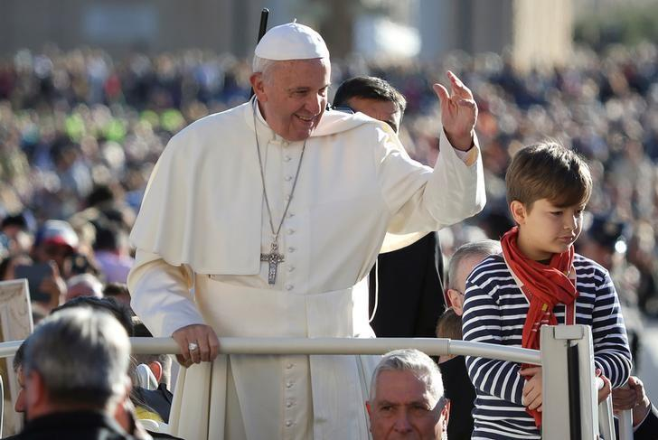 Pope Francis, flanked by a child invited by him to do a tour on his popemobile, arrives to lead his Wednesday general audience in Saint Peter's square at the Vatican October 12, 2016. REUTERS/Alessandro Bianchi