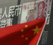 Una bandera china frente a un billete de 100 yuanes, en una sucursal de un banco en un distrito comercial en Pekín, China. 21 de agosto de 2016. Las empresas chinas se preparan para anunciar planes de reestructuración de su deuda tras la publicación el lunes de orientaciones gubernamentales, mientras las autoridades experimentan medidas para contener la creciente deuda corporativa del país. REUTERS/Kim Kyung-Hoon