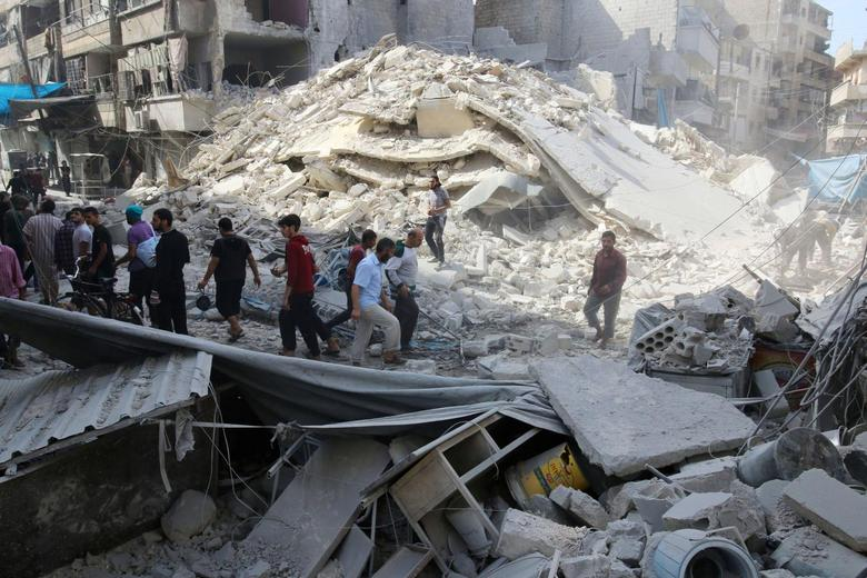 People inspect the damage at a market hit by airstrikes in Aleppo