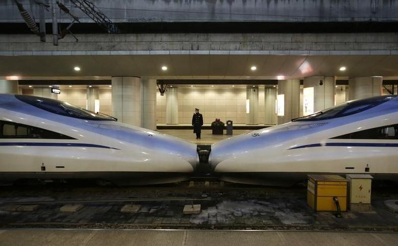 A conductor stands next to a train inside the Beijing West Railway Station, in Beijing, China, February 1, 2016. REUTERS/Jason Lee