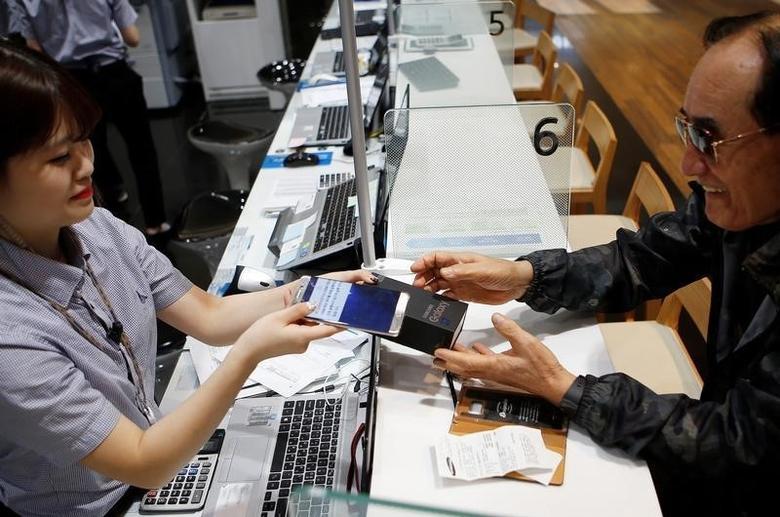 2016年10月13日,在位于首尔的三星电子总部,一名顾客将自己的盖乐世Note7手机置换成盖乐世S7手机。REUTERS/Kim Hong-Ji