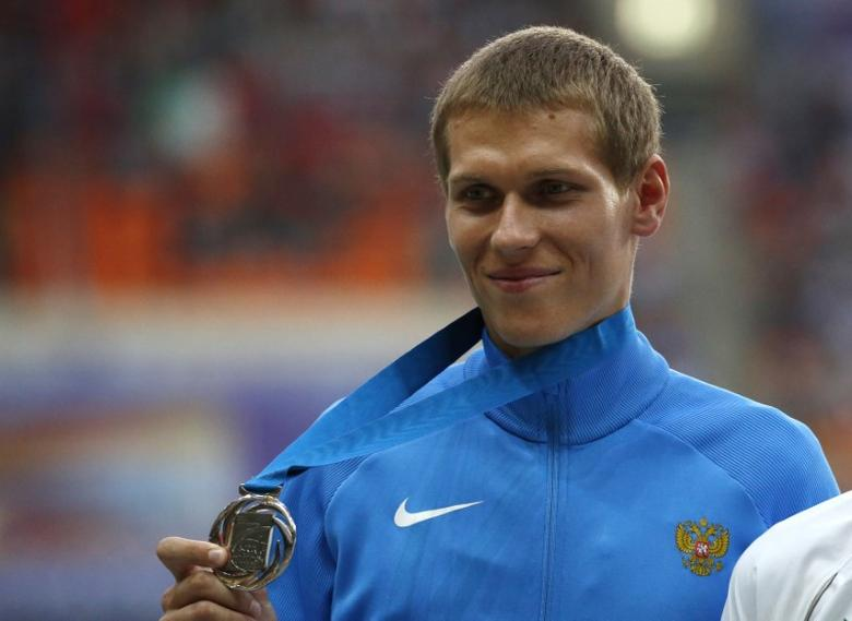 Silver medallist Mikhail Ryzhov of Russia smiles as he holds his medal at the men's 50 km race walk victory ceremony during the IAAF World Athletics Championships at the Luzhniki stadium in Moscow August 15, 2013.     REUTERS/Grigory Dukor
