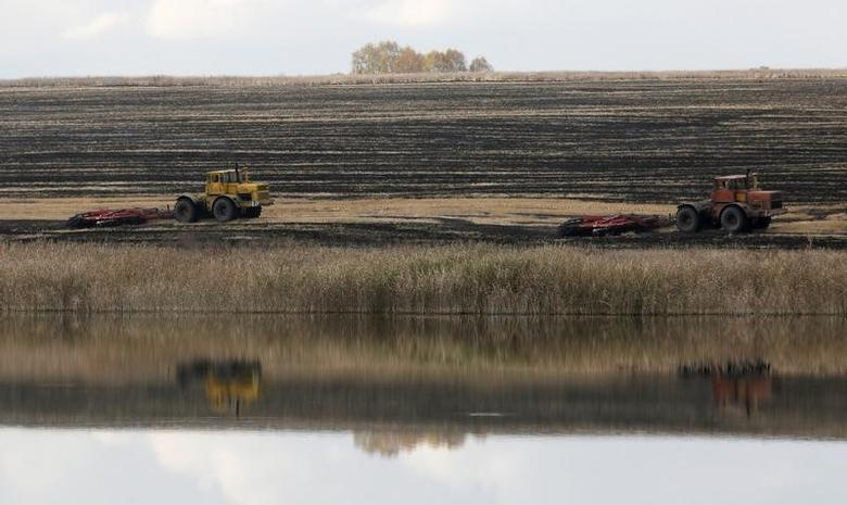 Tractors plough the arable land on an agrarian field on the bank of the Kurganskoye lake near Kurgany village in Krasnoyarsk region, Russia, October 11, 2016.  REUTERS/Ilya Naymushin