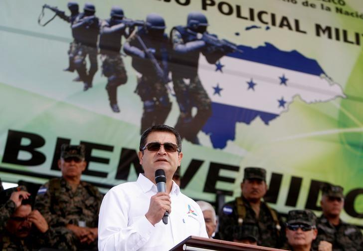 Honduran President Juan Orlando Hernandez gives a speech next to members of the Military Police for Public Order in a ceremony to celebrate the third anniversary of the creation of the Military Police, in Tegucigalpa, Honduras August 24, 2016. REUTERS/Jorge Cabrera/File Photo
