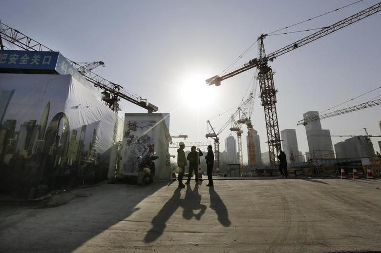 2014年12月29日,北京中央商务区,一处建筑工地旁的工人们。REUTERS/Jason Lee