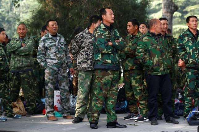 10月14日、中国軍機関紙は、兵力削減を含む軍の改革について「敵対勢力」がネットでうわさを拡散しようとしていると主張した。写真は北京の国防省前で11日にデモを行った退役軍人ら(2016年 ロイター/THOMAS PETER)