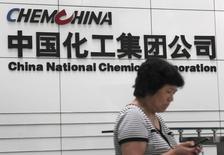Una mujer revisa su celular en la sede de ChemChina en Pekín. 20 de julio de 2009. Las compañías estatales chinas Sinochem Group y ChemChina están en negociaciones sobre una posible fusión que crearía un gigante de la industria de productos químicos y fertilizantes con ingresos anuales de unos 100.000 millones de dólares, dijeron tres fuentes familiarizadas con el asunto. REUTERS/Stringer/File Photo