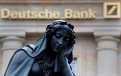 Una estatua junto a un logo del banco alemán Deutsche Bank en Fráncfort, el 26 de enero de 2016. El jefe de finanzas de Deutsche Bank dijo el mes pasado a representantes de los trabajadores que los recortes de empleo en el banco alemán pueden ser el doble de lo planeado, una decisión que podría eliminar otros 10.000 puestos de trabajo, dijo una fuente con conocimiento directo del asunto a Reuters. REUTERS/Kai Pfaffenbach