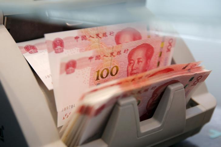Chinese 100 yuan banknotes are seen in a counting machine while a clerk counts them at a branch of a commercial bank in Beijing, China, in this March 30, 2016 file picture. REUTERS/Kim Kyung-Hoon/Files
