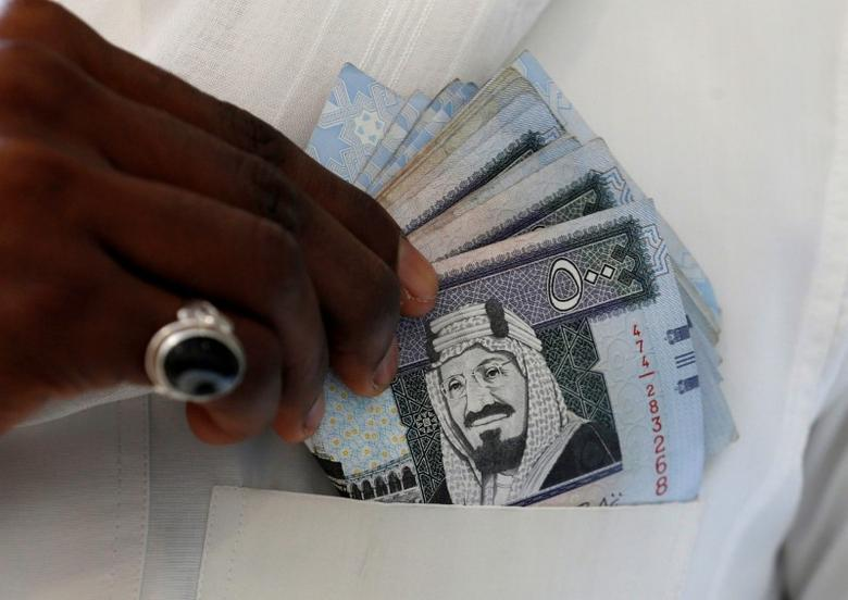A Saudi man shows Saudi riyal banknotes at a money exchange shop, in Riyadh, Saudi Arabia, January 20, 2016. REUTERS/Faisal Al Nasser/File Photo