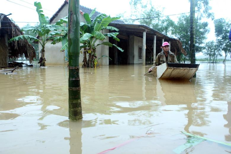 A man paddles a boat near his submerged house during a flood in Vietnam's central Ha Tinh province, October 15, 2016. Mandatory credit VNA/Tuan Anh/via REUTERS