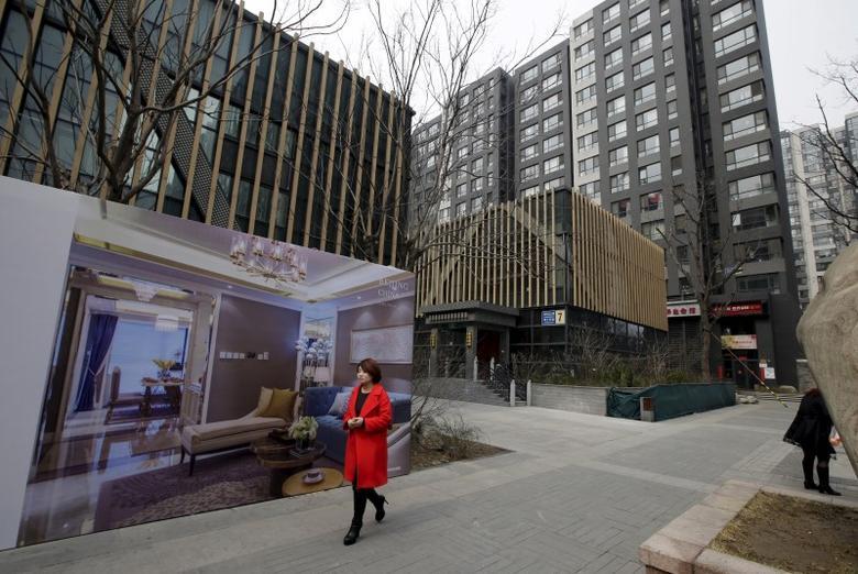 2016年3月15日,中国北京,一名女子走过一处高档住宅小区外的海报。REUTERS/Jason Lee