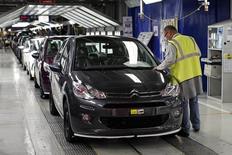 Un trabajador realiza el chequeo final a un auto en la planta de Peugeot en Poissy, cerca de París. 29 de abril de 2015 . PSA Peugeot Citroen planea recortar más de 2.000 puestos de trabajo, alrededor del 3 por ciento de su fuerza laboral, en Francia el año próximo a través de una combinación de jubilaciones anticipadas y retiros voluntarios, informó el lunes la radio France Info, citando documentos internos. REUTERS/Benoit Tessier