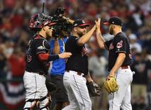 Cleveland Indians catcher Roberto Perez (55) high fives first baseman Mike Napoli (26) and relief pitcher Cody Allen (37) after defeating the Toronto Blue Jays in game two of the 2016 ALCS playoff baseball series at Progressive Field. Cleveland won 2-1. Mandatory Credit: Ken Blaze-USA TODAY Sports