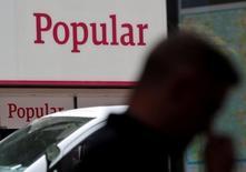 Banco Popular dijo el martes que estudia recomprar la gestora inmobiliaria Aliseda dentro del proceso de desconsolidación de activos inmobiliarios. En la imagen, un hombre pasa junto a una sucursal de Banco Popular en Madrid, el 26 de mayo de 2016. REUTERS/Andrea Comas/File Photo