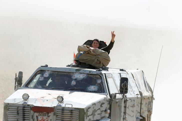 A member of Peshmerga forces gestures from the top of the military vehicle in the east of Mosul during operation to attack Islamic State militants in Mosul, Iraq, October 18, 2016. REUTERS/Thaier Al-Sudani