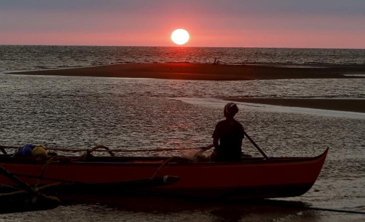 A fisherman watches sunset in the  South China Sea, about 130 nautical miles from Scarborough Shoal in the coastal town of Masinloc, Zambales in northern Philippines April 21, 2015. REUTERS/Erik De Castro/File Photo