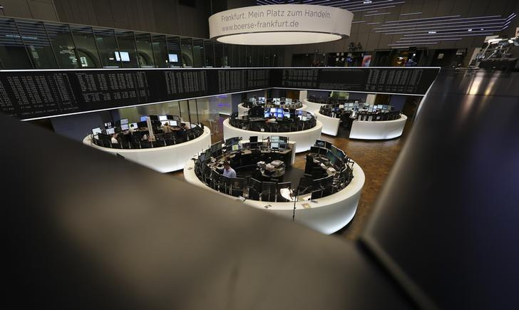 Traders work at their desks in front of the German share price index, DAX board, at the stock exchange in Frankfurt, Germany, October 14, 2016.  REUTERS/Kai Pfaffenbach