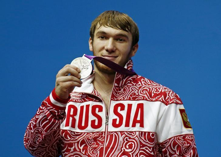 Russia's Apti Aukhadov pose with his silver medal at the podium of the men's 85Kg weightlifting competition at the ExCel venue at the London 2012 Olympic Games August 3, 2012.  REUTERS/Dominic Ebenbichler/File Photo