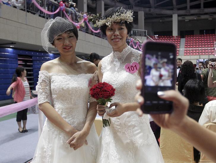 A same-sex couple poses for a picture during a mass wedding ceremony in Taipei, Taiwan, October 24, 2015. REUTERS/Pichi Chuang/File Photo