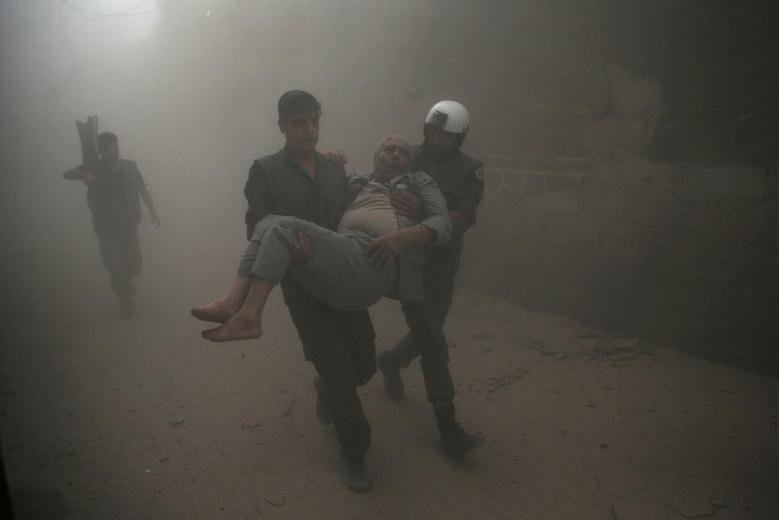 Civil defense members carry an injured man after an air strike in the rebel-held Douma neighbourhood of Damascus, Syria October 12, 2016. REUTERS/Bassam Khabieh     TPX IMAGES OF THE DAY