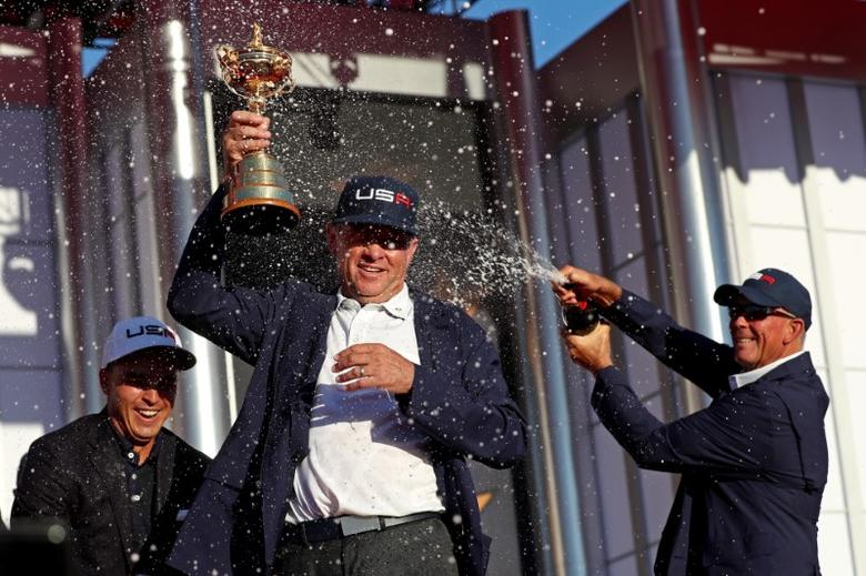 Oct 2, 2016; Chaska, MN, USA; Team USA captain Davis Love III celebrates with the Ryder Cup as Team USA vice-captain Tom Lehman sprays champagne during the closing ceremonies after the single matches in 41st Ryder Cup at Hazeltine National Golf Club. Mandatory Credit: Rob Schumacher-USA TODAY Sports