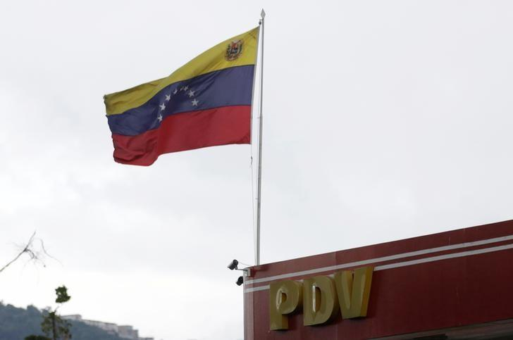 The logo of a subsidiary of the Venezuelan state oil company PDVSA is seen next to Venezuela's flag at a gas station in Caracas, Venezuela, September 13, 2016. REUTERS/Henry Romero